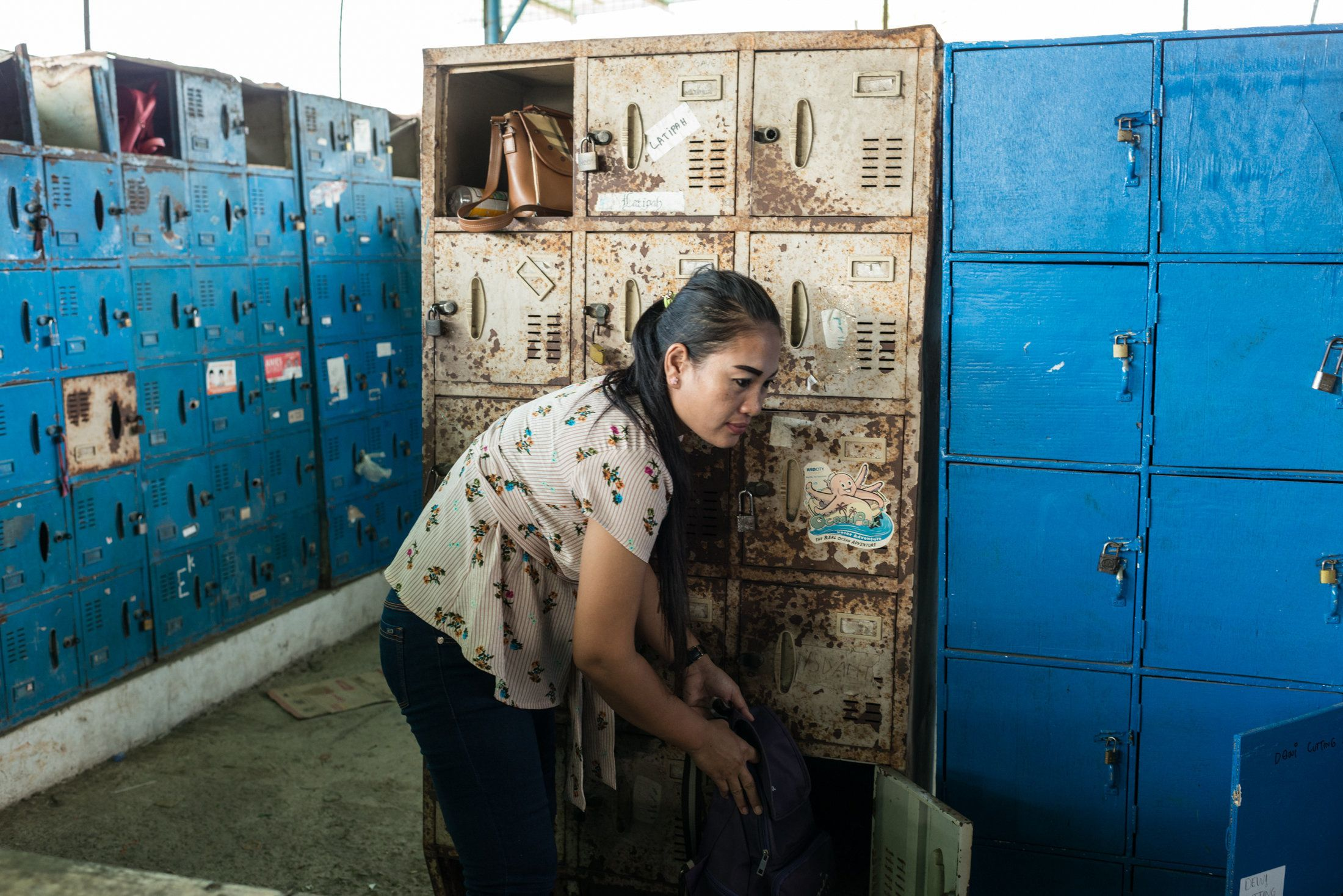 Istiyaroh, 35, an employee at Kaho Indah Citra Garment factory in North Jakarta, collects her bag from a locker when she fini