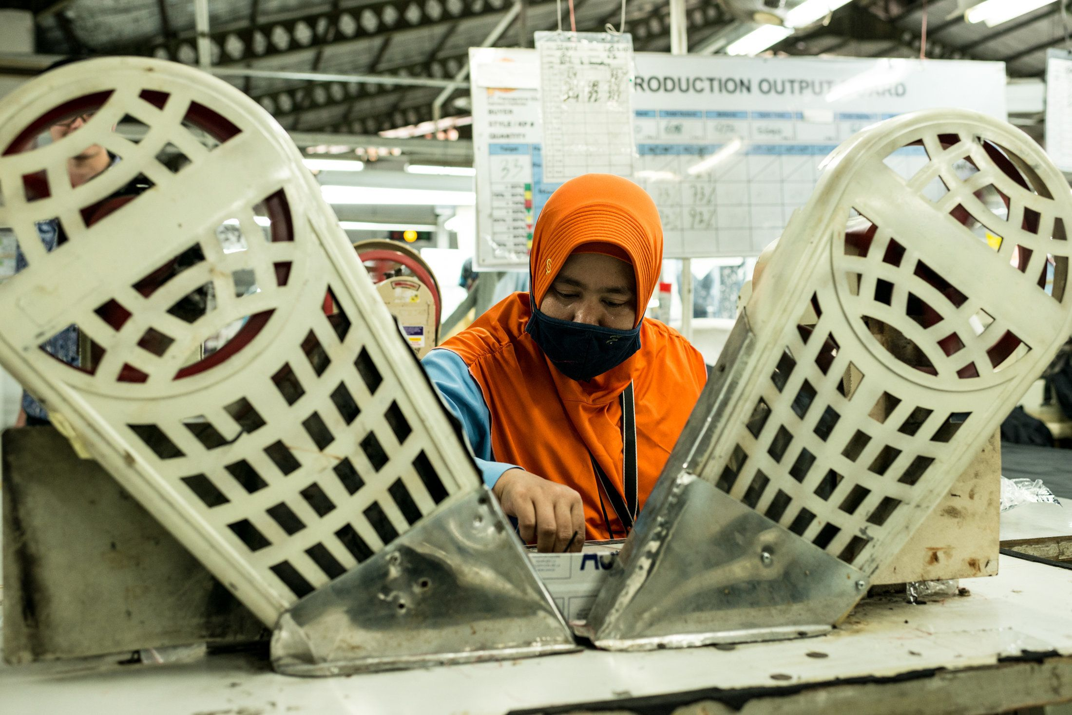 A worker sits at a machine for stitching buttons on jackets and pants, at Pan Brothers garment factory in Tangerang