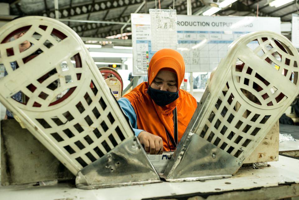 Una trabajadora, sentada en una máquina para coser botones en chaquetas y pantalones, en una fábrica...