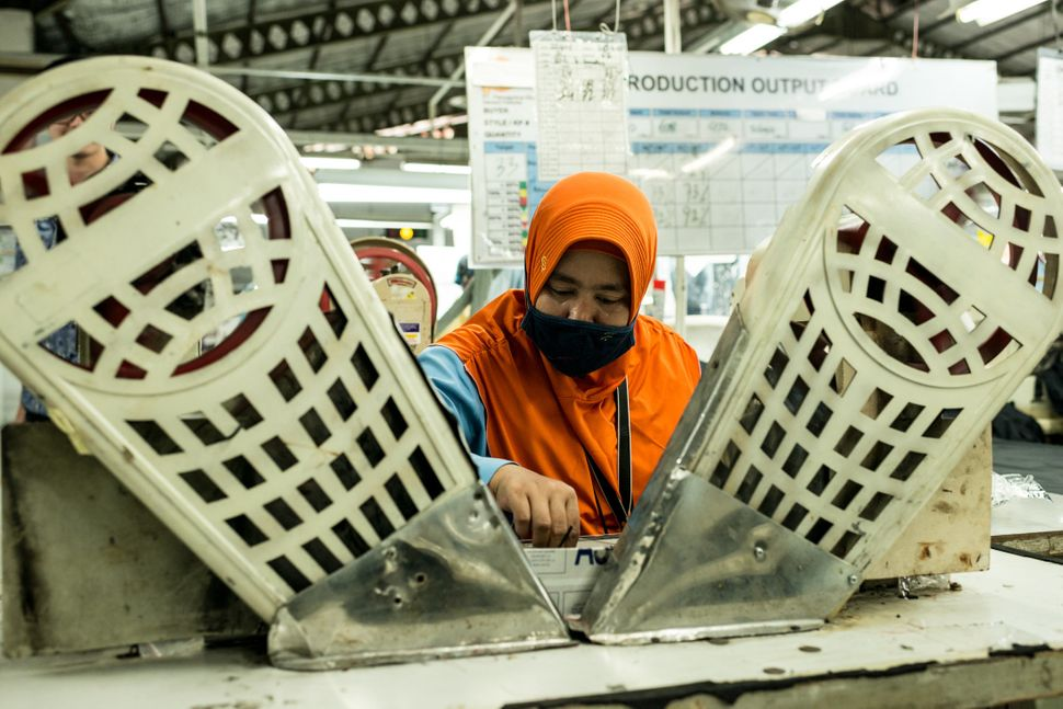 A worker sits at a machine for stitching buttons on jackets and pants, at Pan Brothers garment...