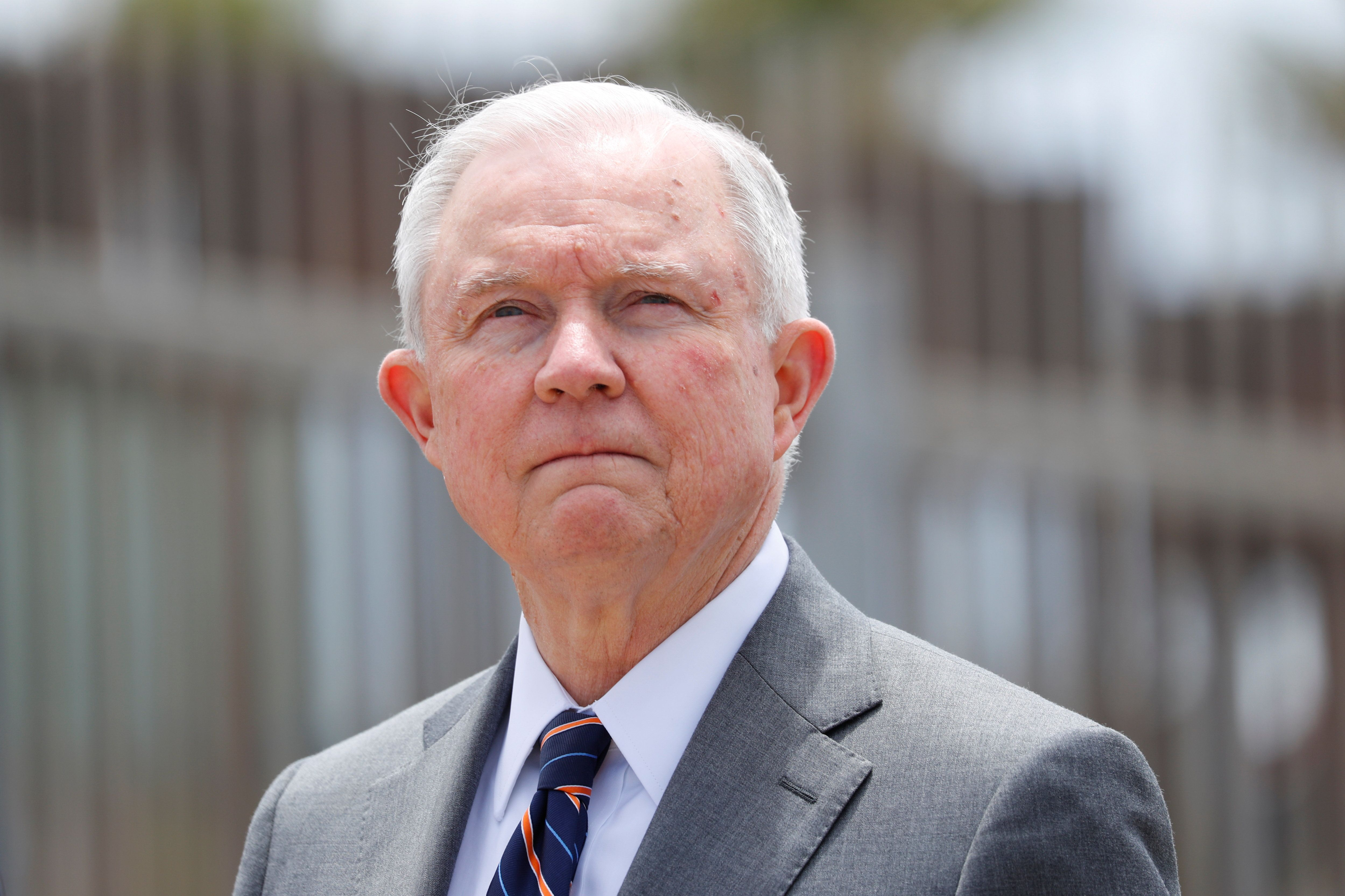 U.S. Attorney General Jeff Sessions looks on during a news conference next to the U.S. Mexico border wall to discuss immigration enforcement actions of the Trump Administration near San Diego, California, U.S. May 7, 2018.   REUTERS/Mike Blake