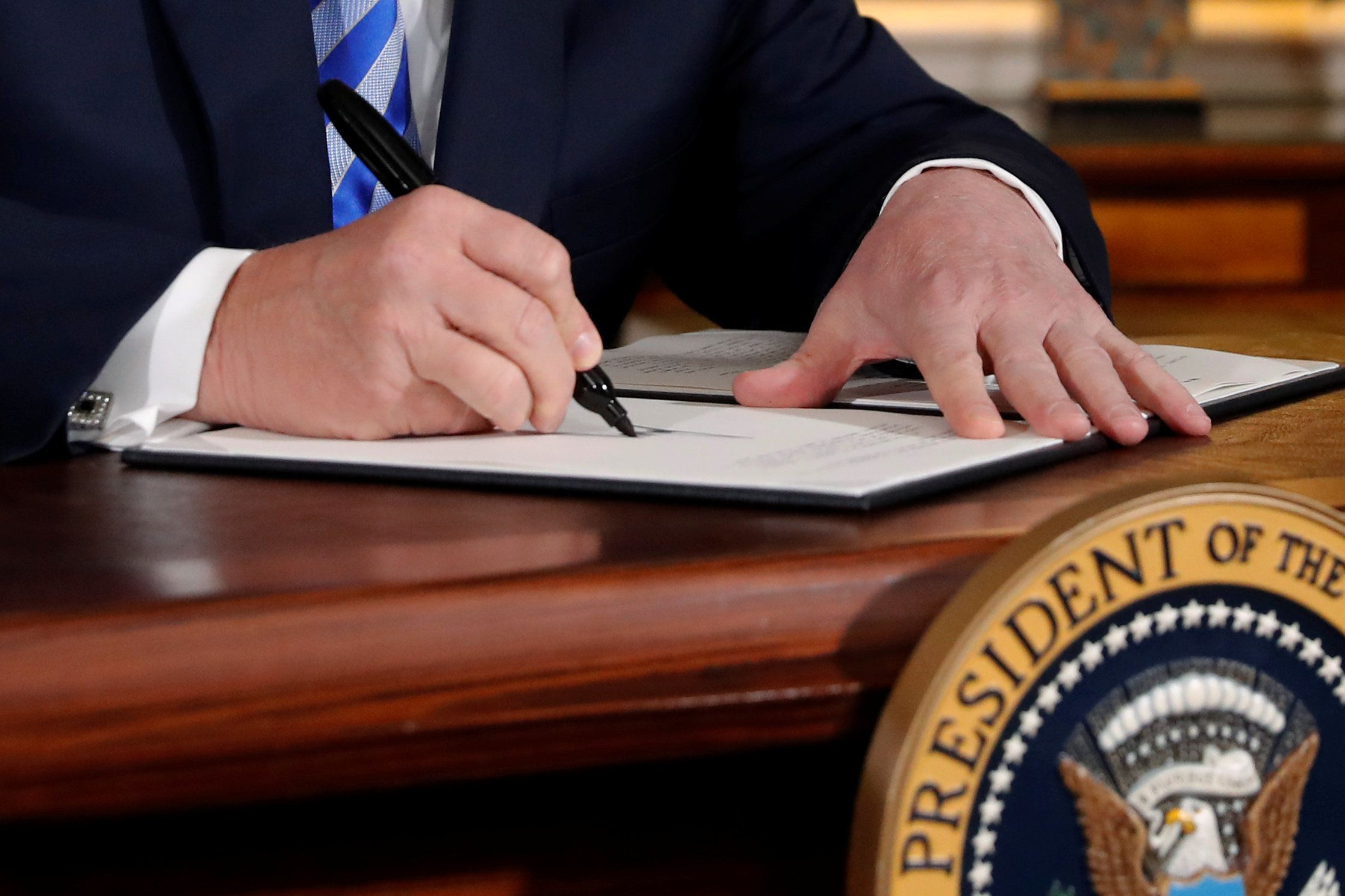 U.S. President Donald Trump signs a proclamation declaring his intention to withdraw from the JCPOA Iran nuclear agreement in the Diplomatic Room at the White House in Washington, U.S. May 8, 2018.  REUTERS/Jonathan Ernst