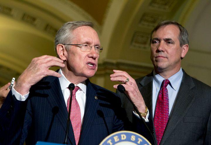 Then-Senate Majority Leader Harry Reid (D-Nev.) speaks to reporters after Senate luncheons as he is accompanied by Sen. Jeff