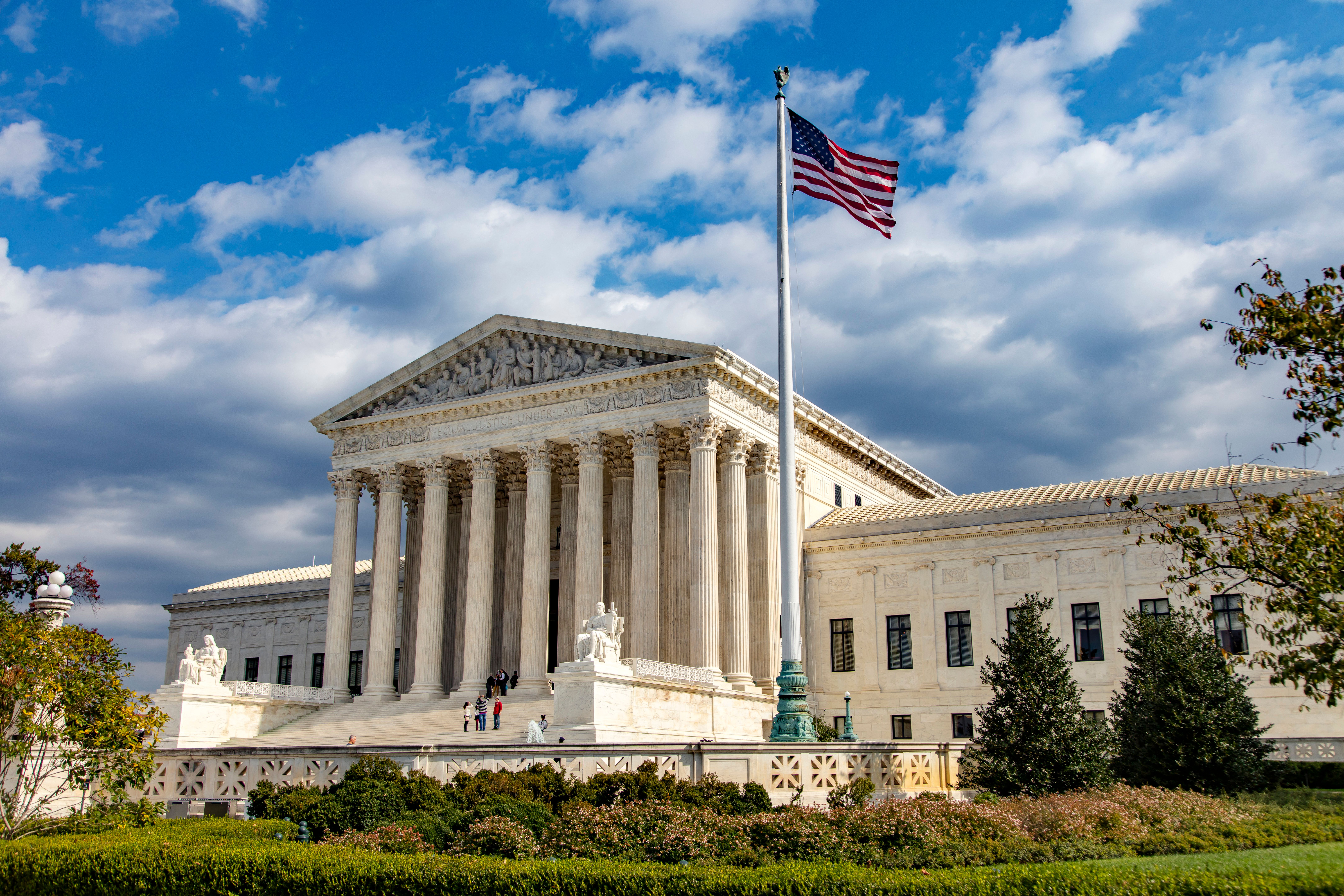 An angular, landscape view of the US Supreme Court building in Washington DC. The few people in the image are on the steps leading up to the entrance.