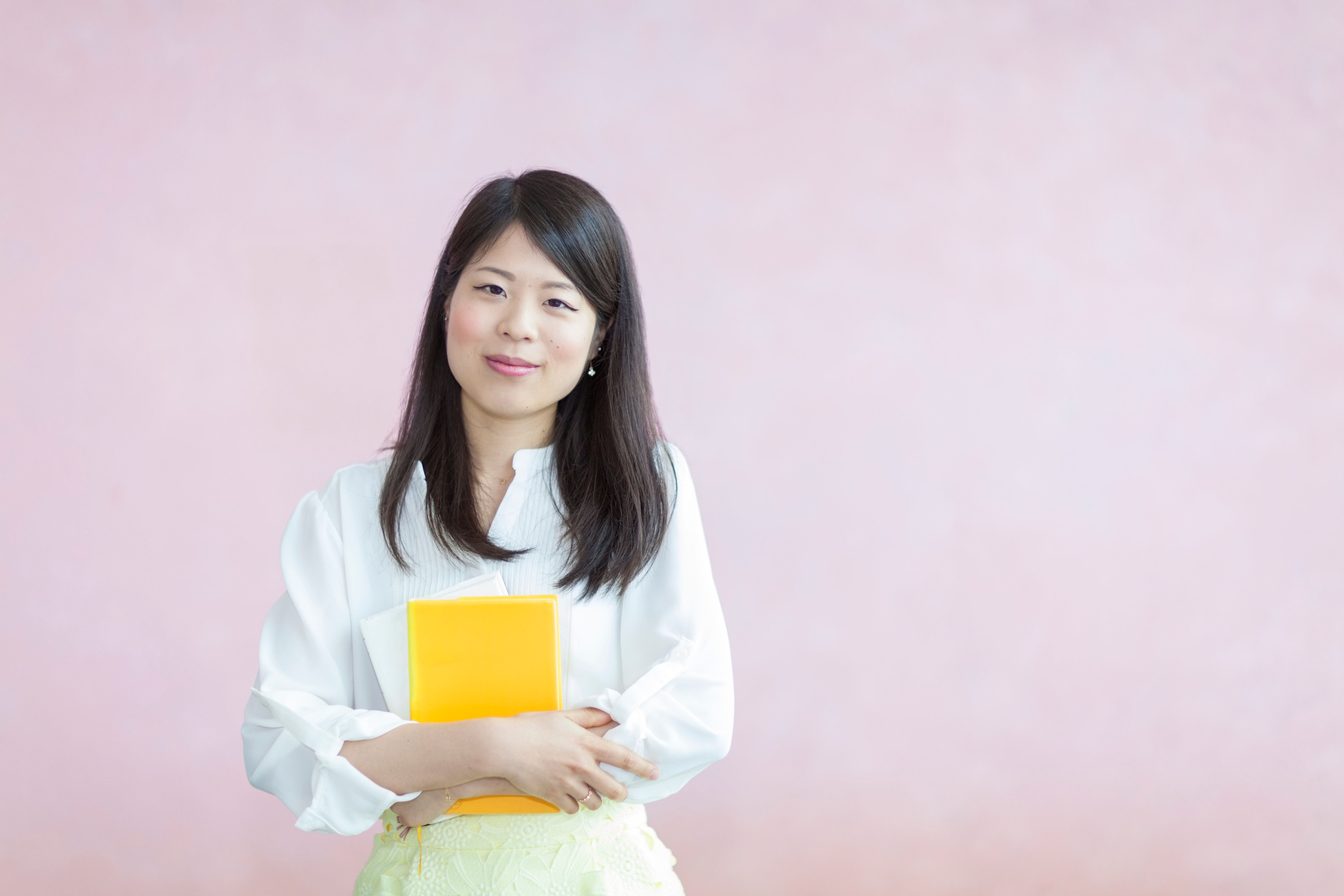 A young Japanese female student is holding books and looking at the camera happily in fron of a pink background.