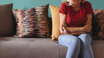 Mature or senior woman in her late 50s having pelvic pain while doing houseworks or during resting. Woman is going through the pain and suffer due to pelvic inflammatory disease.