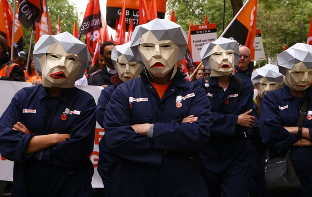 People dressed as Theresa May Bots during a TUC rally in central London, as part of its 'great jobs'