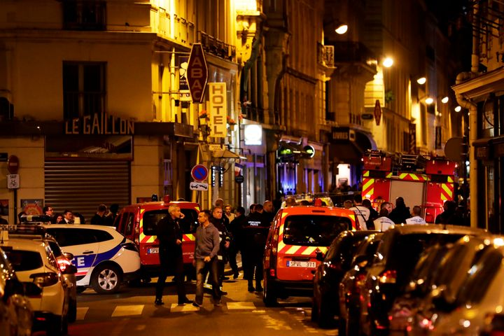 Policemen and emergency responders stand in a blocked street in Paris near the site of Saturday's knife attack.