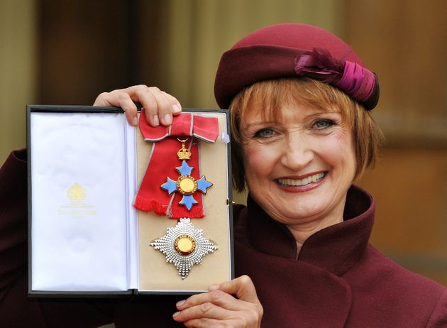 Dame Tessa proudly holding her Dame Commander insignia in
