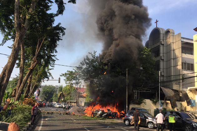 Motorcycles burn following a blast at the Pentecost Church Central Surabaya (GPPS), in Surabaya, East...