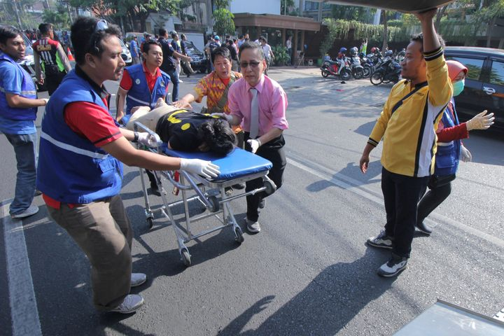 A person injured from a blast at the Indonesian Christian Church is evacuated to a waiting ambulance in Surabaya, East Java,