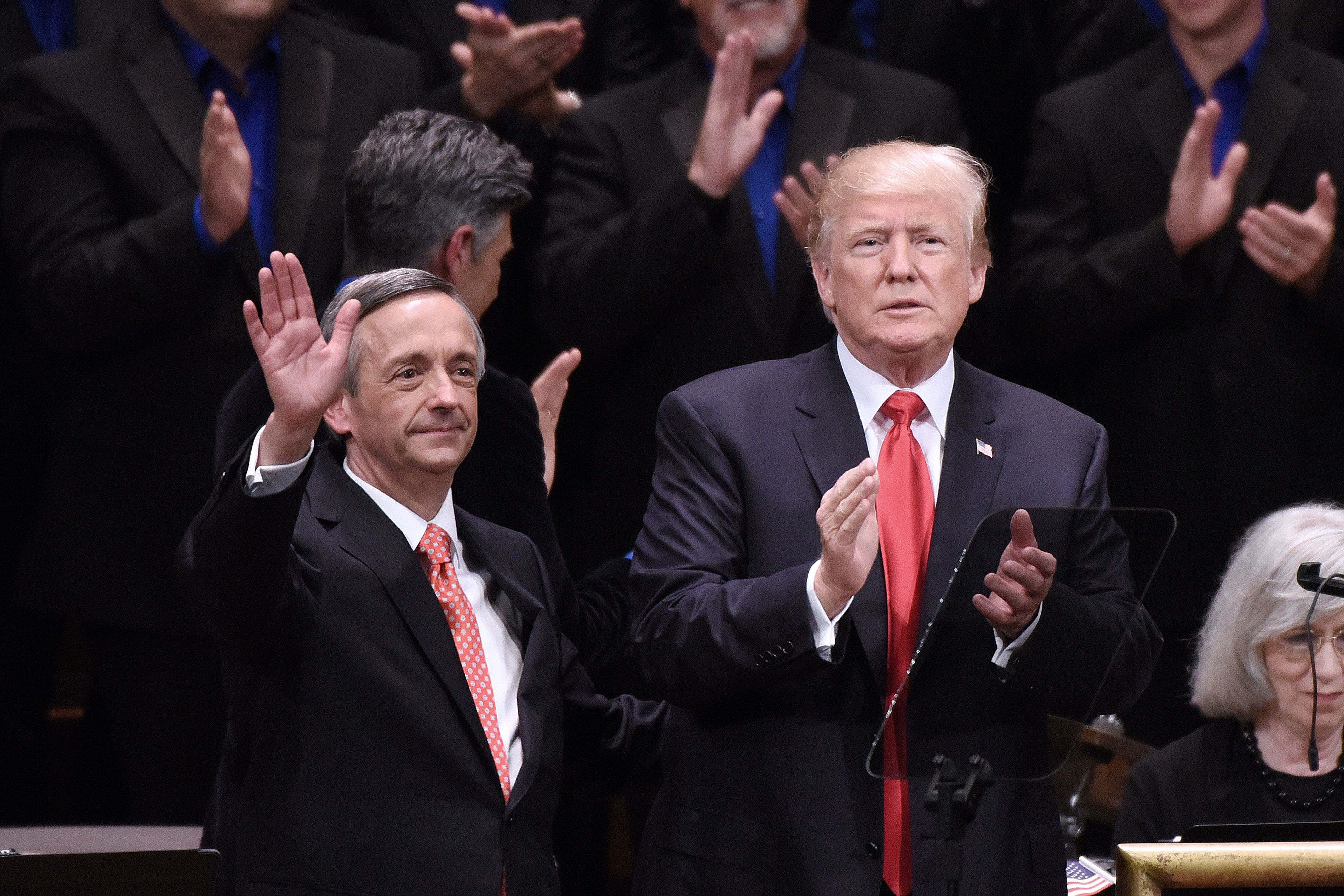 U.S. President Donald Trump, right, applauds as pastor Robert Jeffress waves during the 'Celebrate Freedom' event at the John F. Kennedy Center for the Performing Arts in Washington, D.C., U.S., on Saturday, July 1, 2017. Trump returned to the relatively calm waters of patriotism and supporting American troops in a speech on Saturday night that followed several outbursts against the media and others on social media earlier in the day. Photographer: Olivier Douliery/Bloomberg via Getty Images