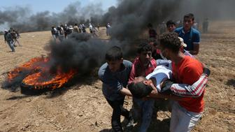 A wounded Palestinian demonstrator is evacuated during a protest against U.S. embassy move to Jerusalem and ahead of the 70th anniversary of Nakba, at the Israel-Gaza border in the southern Gaza Strip May 14, 2018. REUTERS/Ibraheem Abu Mustafa