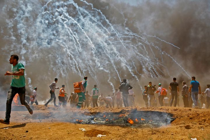 Palestinians run for cover from tear gas during clashes with Israeli security forces near the border between Israel and the G
