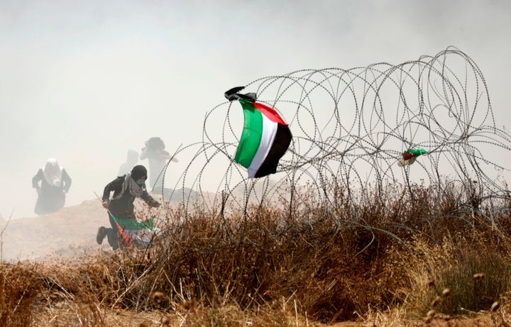 A Palestinian protester holding his national flag runs past barbed wires during clashes with Israeli forces near the border b