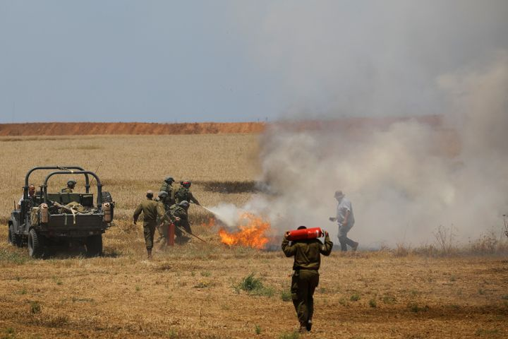Israeli soldiers attempt to extinguish a fire in a field on the Israeli side of the border fence between Israel and Gaza near