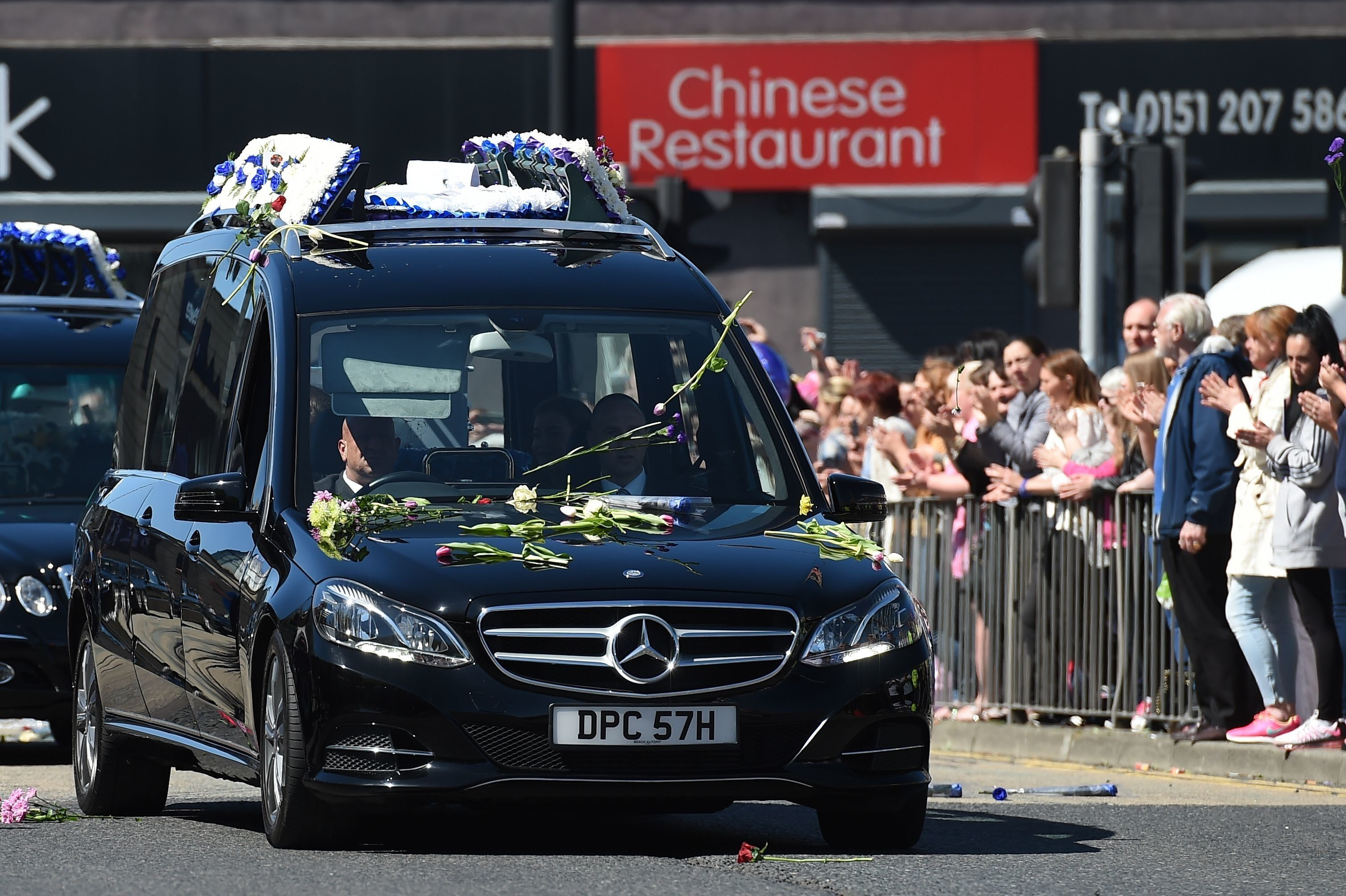 PAUL ELLIS via Getty Images                   Crowds clapped and threw flowers as the funeral cortege drove past