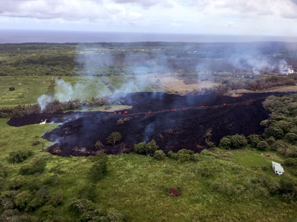 In this handout photo provided by the U.S. Geological Survey, a lava flow emerges from a fissure as a result of Kilauea volca