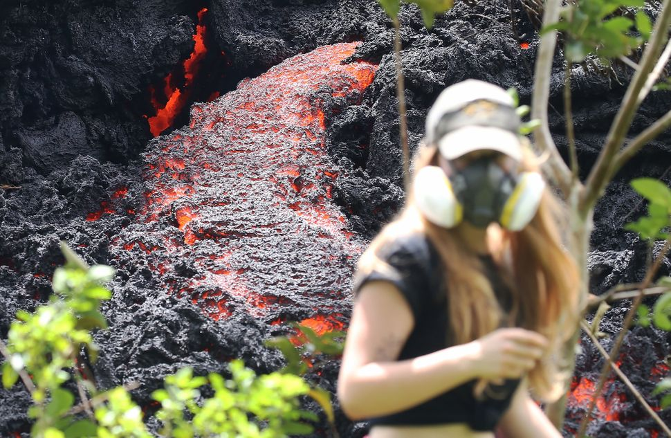 Lava flows at a new fissure in the aftermath of eruptions from the Kilauea volcano on Hawaii's Big Island as a local resident