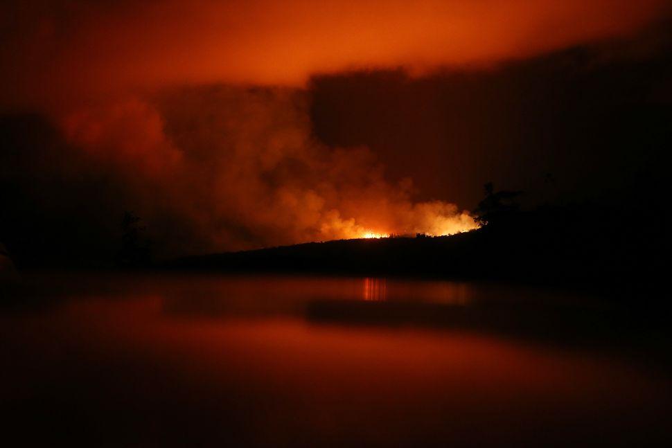 The latest Kilauea volcano activity illuminates the sky and is reflected off a vehicle (Bottom) on Hawaii's Big Island on May