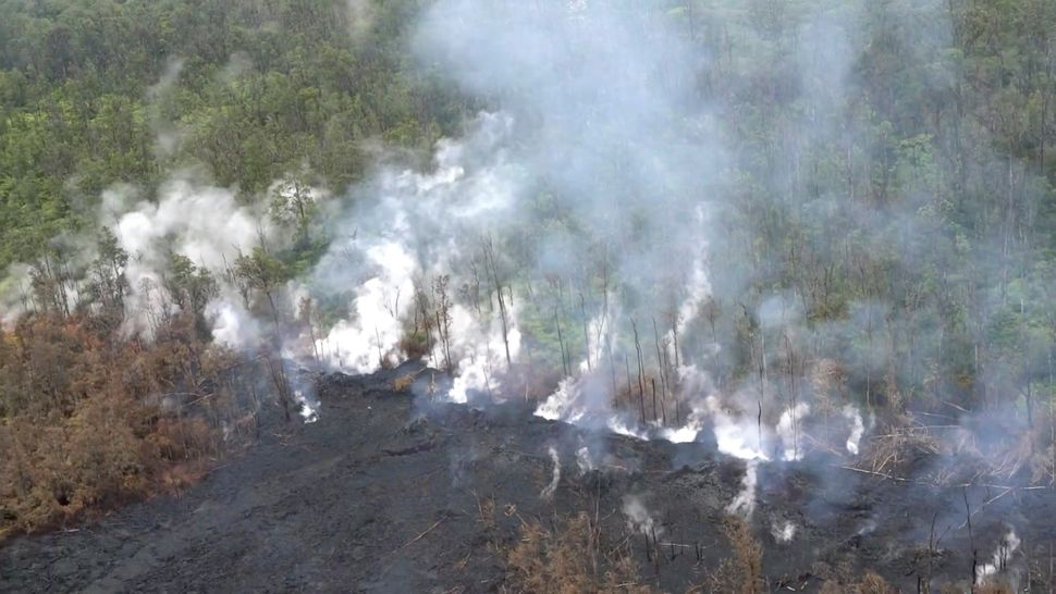 Molten rock flows and burst to the surface, threatening homes in a rural area in this still image from an aerial video taken