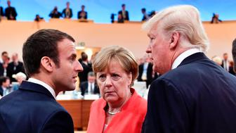 (L-R) French President Emmanuel Macron, German Chancellor Angela Merkel and US President Donald Trump confer as Argentinia's President Mauricio Macri walks past them at the start of the first working session of the G20 meeting in Hamburg, northern Germany, on July 7. Leaders of the world's top economies will gather from July 7 to 8, 2017 in Germany for likely the stormiest G20 summit in years, with disagreements ranging from wars to climate change and global trade. / AFP PHOTO / AFP PHOTO AND POOL / John MACDOUGALL        (Photo credit should read JOHN MACDOUGALL/AFP/Getty Images)