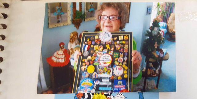 Alice Pirnie holding up some of her McDonald's memorabilia.