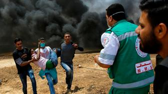 Palestinians carry a wounded protestor during clashes with Israeli security forces near the border between Israel and the Gaza Strip, east of Jabalia on May 14, 2018, as Palestinians protest over the inauguration of the US embassy following its controversial move to Jerusalem. (Photo by MOHAMMED ABED / AFP)        (Photo credit should read MOHAMMED ABED/AFP/Getty Images)