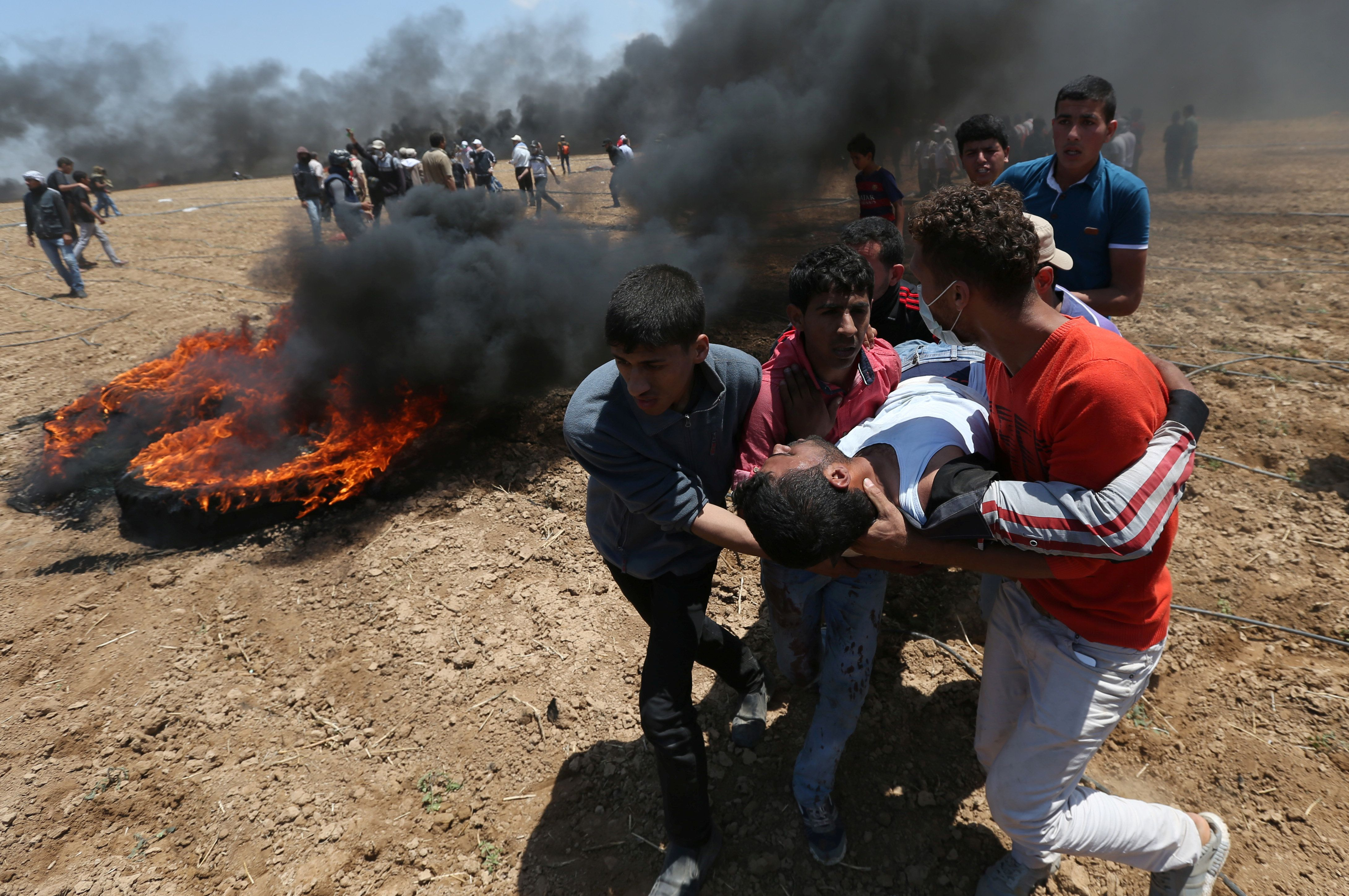 A wounded Palestinian demonstrator is evacuated at the Israel-Gaza border, May 14, 2018.