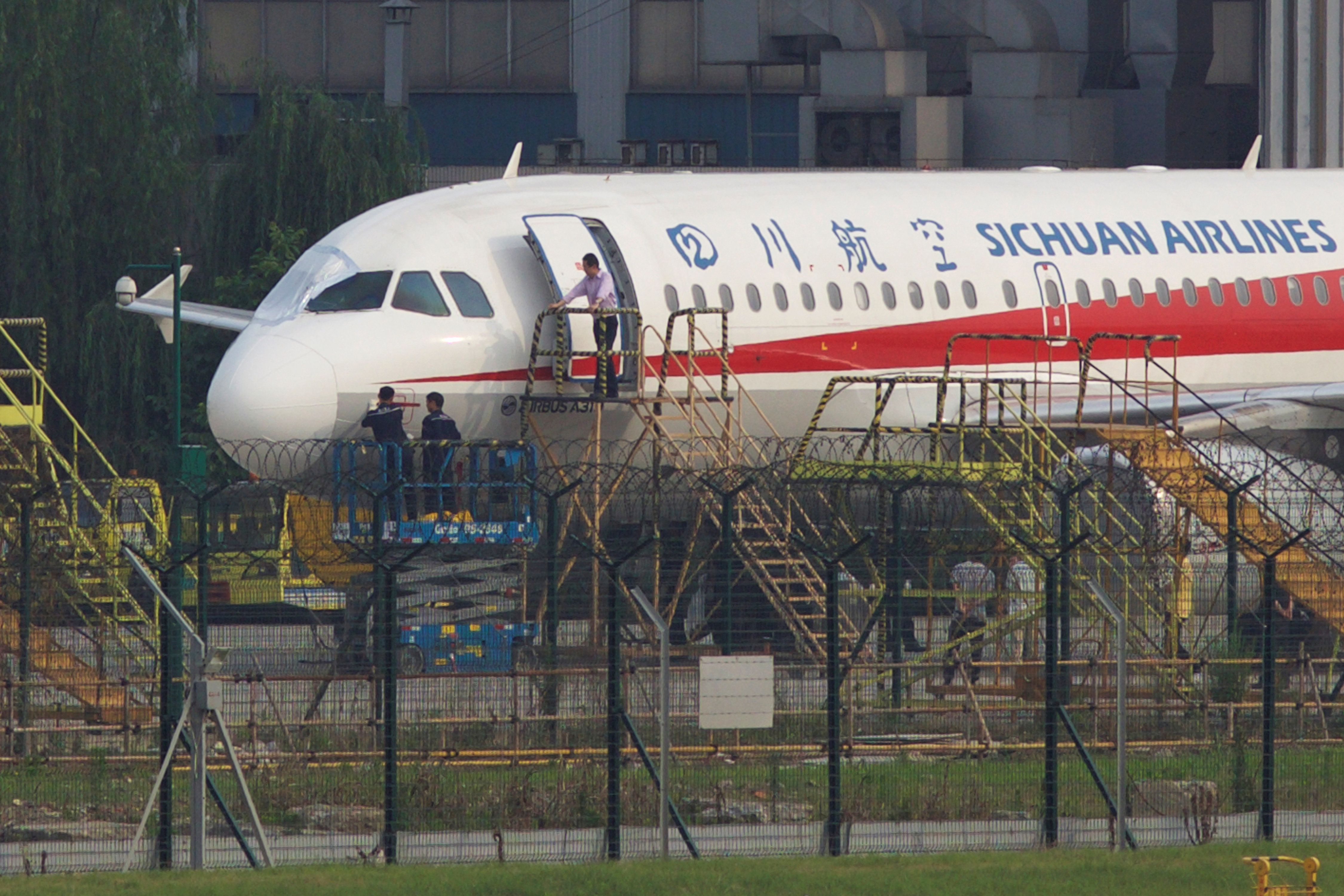 Workers inspect a Sichuan Airlines aircraft that made an emergency landing after a windshield on the cockpit broke off, at an