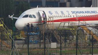 Workers inspect a Sichuan Airlines aircraft that made an emergency landing after a windshield on the cockpit broke off, at an airport in Chengdu, Sichuan province, China May 14, 2018. Picture taken May 14, 2018. REUTERS/Stringer  ATTENTION EDITORS - THIS IMAGE WAS PROVIDED BY A THIRD PARTY. CHINA OUT.     TPX IMAGES OF THE DAY