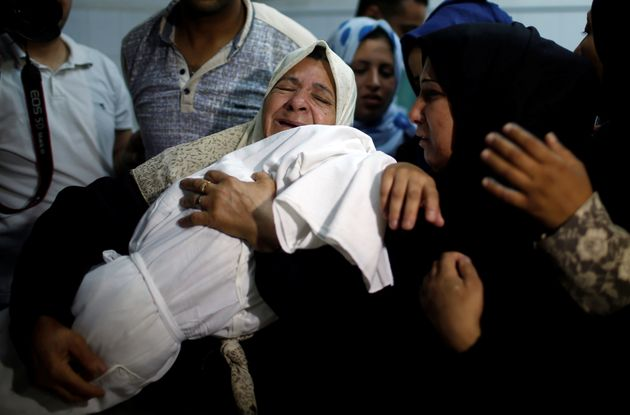 A relative carries the body of 8-month-old Palestinian infant Laila al-Ghandour, who died after inhaling...