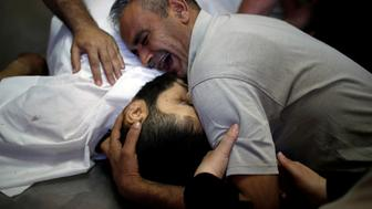 ATTENTION EDITORS - VISUAL COVERAGE OF SCENES OF INJURY OR DEATH The brother of Palestinian Shaher al-Madhoon, who was killed during a protest at the Israel-Gaza border, reacts over his body at a hospital morgue in the northern Gaza Strip May 14, 2018. REUTERS/Mohammed Salem TEMPLATE OUT     TPX IMAGES OF THE DAY