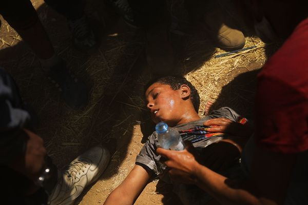 A child overcome by tear gas receives medical help.