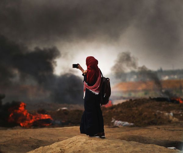 A Palestinian woman documents the situation at the border fence with Israel in Gaza City, Gaza.