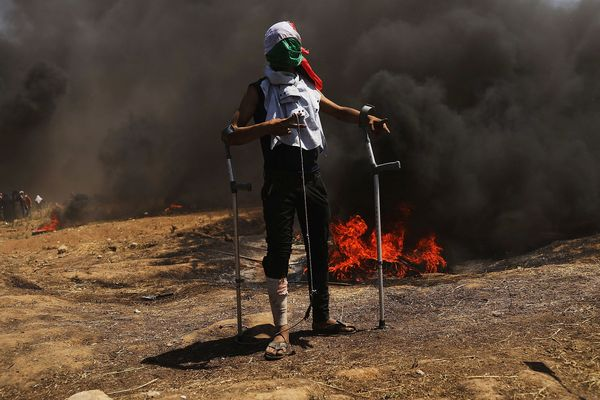 A wounded Palestinian protestor stands at the border fence.