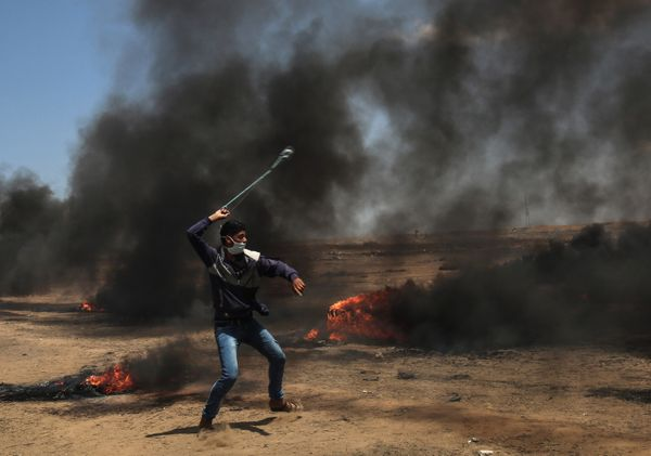 A Palestinian man uses a slingshot during clashes with Israeli forces.