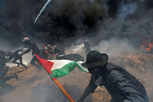 Palestinian demonstrators run for cover from Israeli fire and tear gas.