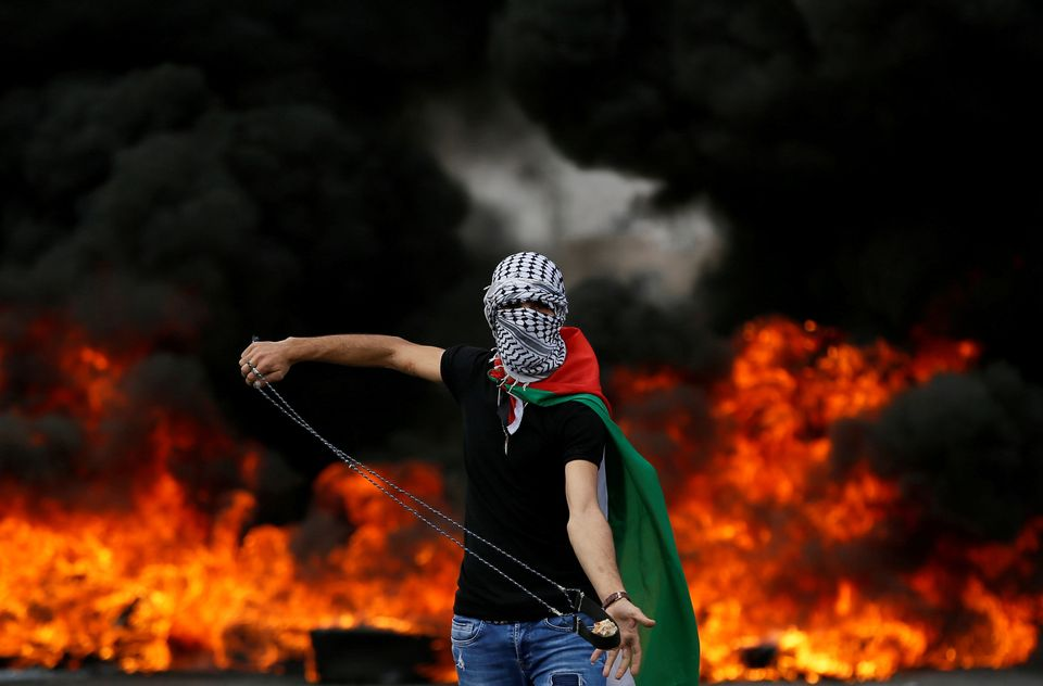 A Palestinian demonstrator holds a sling during a protest marking the 70th anniversary of Nakba, near the Jewish settlement o