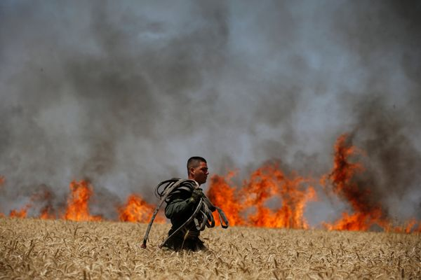An Israeli soldier carries a hose as he walks in a burning field on the Israeli side of the border fence between Israel and G