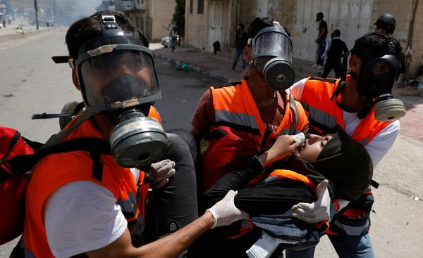 A female Palestinian medic is evacuated after inhaling tear gas fired by Israeli forces.