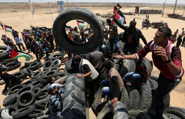 Palestinians collect tires to be burnt.