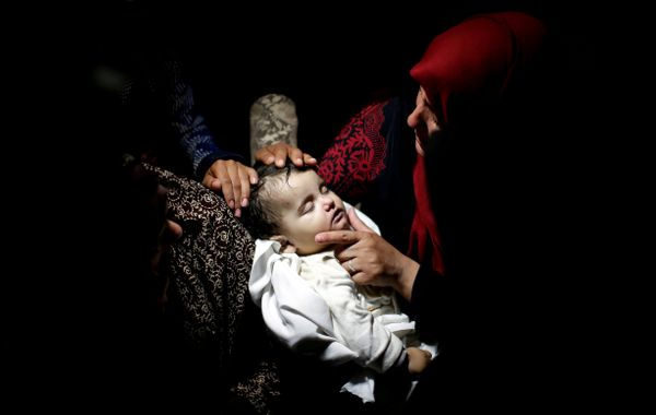 A relative mourns as she carries the body of eight-month-old Palestinian infant Laila al-Ghandour, who died after inhal
