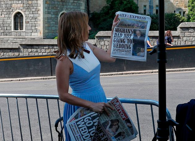 A CNN reporter holds up copies of British newspapers leading with a story on Thomas Markle outside Windsor...