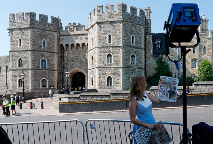 A CNN reporter holds up copies of British newspapers leading with a story on Thomas Markle outside Windsor Castle on May 15.