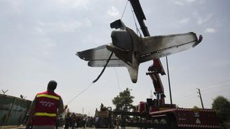 Iranian firemen relocate the remains of a plane as they secure the scene of a crash near Tehran's Mehrabad airport on August 10, 2014. An Iranian passenger plane crashed moments after takeoff from Tehran, killing at least 38 people on board and narrowly avoiding many more deaths when it plummeted to earth near a busy market. AFP PHOTO/BEHROUZ MEHRI        (Photo credit should read BEHROUZ MEHRI/AFP/Getty Images)
