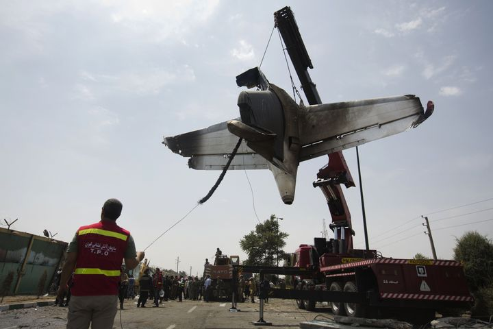 Iranian firefighters relocate the remains of a plane near Tehran's Mehrabad International Airport after a crash in 2014.