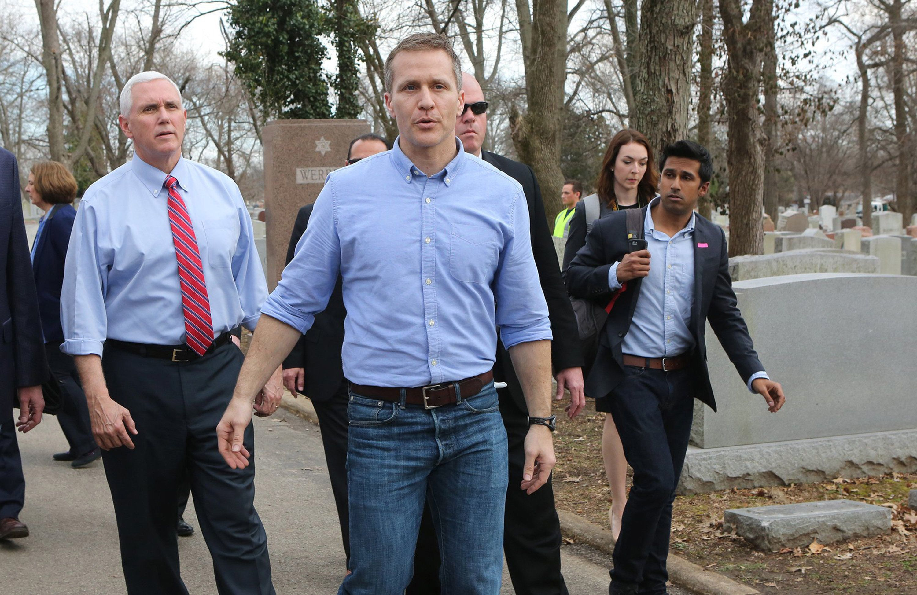 Vice President Mike Pence and Missouri Gov. Eric Greitens walk through the Chesed Shel Emeth Cemetery in University City, Mo., on Wednesday, Feb. 22, 2017, after viewing some of the damage done last weekend when more than 150 headstones were overturned. Pence has postponed a trip to Missouri that falls before Greiten's criminal trial. (J.B. Forbes/St. Louis Post-Dispatch/TNS via Getty Images)