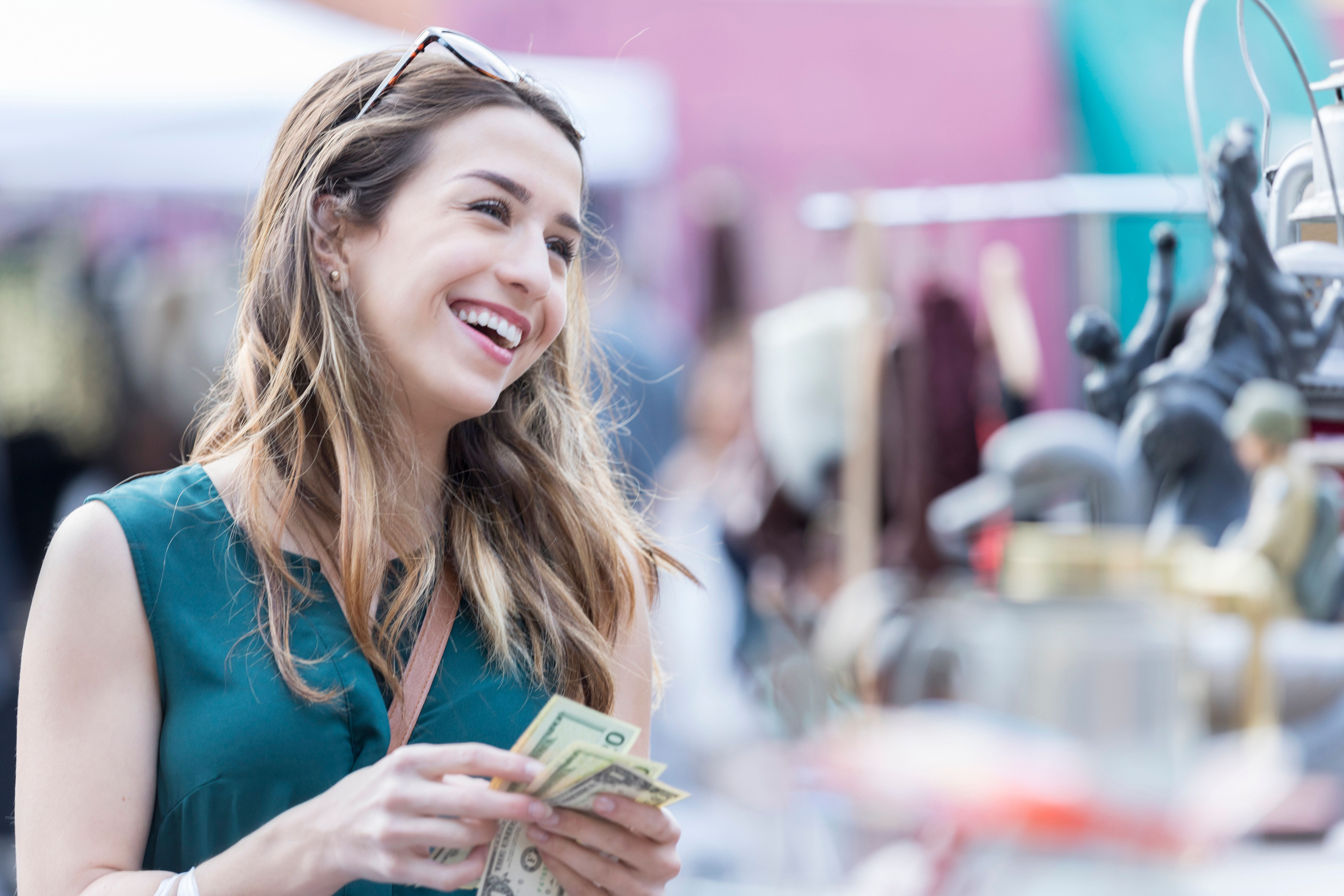 A smiling young woman holds paper currency ready to make a purchase in an outdoor street shop in New York City.
