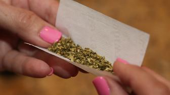 BETHPAGE, NY - AUGUST 30:  A woman rolls a marijuana cigarette as photographed on August 30, 2014 in Bethpage, New York.  (Photo by Bruce Bennett/Getty Images)